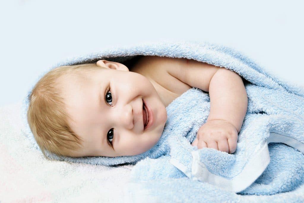 niño rubio con toalla azul